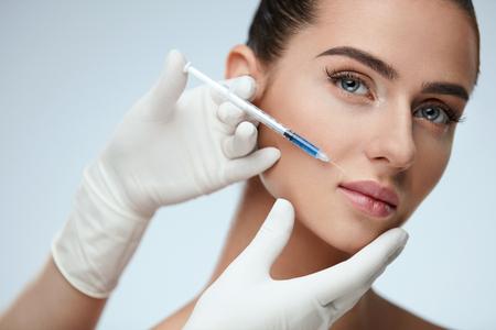 Chirurgia plastica. Primo piano dell'iniezione del labbro ialuronico del dottore Hands Doing Beauty per le labbra sexy della ragazza. Ritratto di bella giovane donna che ottiene trattamento cosmetico all'interno. Procedura per la pelle. Alta risoluzione Archivio Fotografico - 75849458