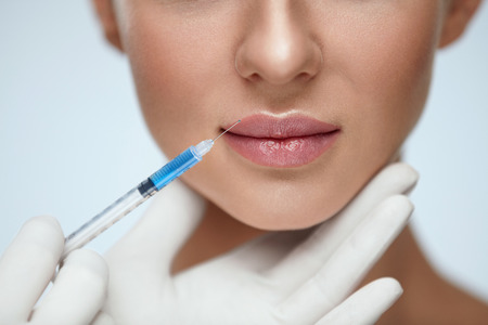 Lip Augmentation. Beautiful Young Womans Mouth Receiving Hyaluronic Acid Injection. Closeup Of Beautician Hands Doing Beauty Procedure To Sexy Female Lips. Cosmetology Treatment. High Resolution Stock Photo