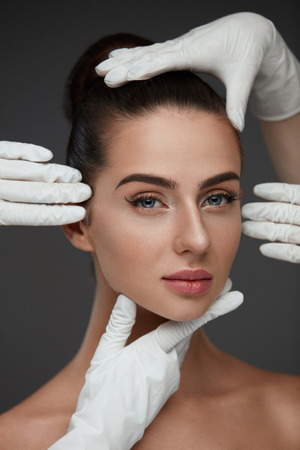 Beauty Face. Beautiful Woman Before Plastic Surgery Operation. Closeup Hands In Gloves Touching Female Head. Portrait Of Young Woman With Smooth Facial Skin. Cosmetology And Skin Care. High Resolution