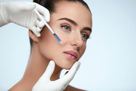 Cirugía plástica. Primer de las manos del esteticista que sostienen la jeringuilla cerca de la inyección facial femenina de la piel que hace inyecciones. Retrato de la cara hermosa de la mujer joven que consigue la inyección hialurónica. Cosmetología. Alta resolución Foto de archivo - 75849301