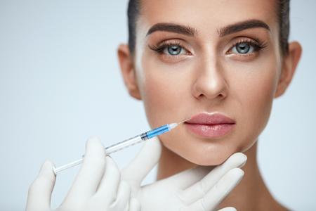 Plastische chirurgie. Close-up van Arts Hands Doing Beauty Hyaluronic Lip Injection voor Sexy Girl Lips. Portret van mooie jonge vrouw cosmetische behandeling binnenshuis krijgen. Huidprocedure. Hoge resolutie