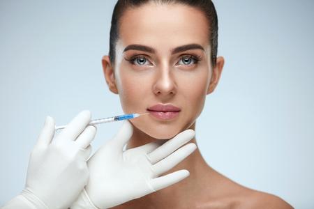 Schoonheid injectie. Close-up van Arts Hands With Syringe Near Female Face. Portret van mooie vrouw met zachte huid, perfecte make-up ontvangen gezichtshuid lifting behandeling, injecties. Hoge resolutie