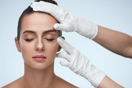 Tratamiento facial. Retrato de la mujer atractiva con los ojos cerrados y líneas quirúrgicos negros en la piel. Primer de las manos que tocan joven rostro femenino. Concepto de Cirugía Plástica. Alta resolución Foto de archivo