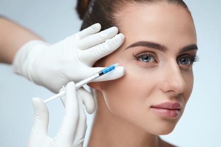 Schoonheidszorg. Portret van mooie jonge vrouw krijgt hyaluron injectie in gezicht. Closeup gezonde vrouw met gladde huid en perfecte make-up ontvangen gezicht huid lift injecties. Hoge resolutie Stockfoto - 75849313