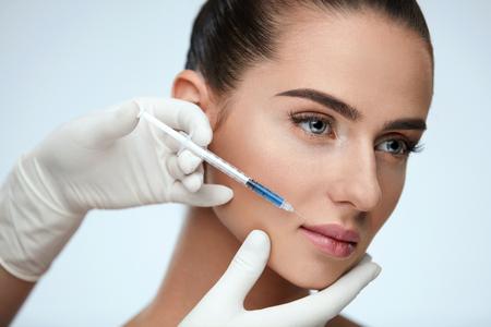 整形手術。注射器注射をして女性の顔の皮膚近くを保持している美容師の手のクローズ アップ。ヒアルロン注射を得て美しい若い女性の顔の肖像画