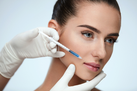 Plastic Surgery. Closeup Of Beautician Hands Holding Syringe Near Female Facial Skin Doing Injections. Portrait Of Beautiful Young Woman Face Getting Hyaluronic Injection. Cosmetology. High Resolution Archivio Fotografico