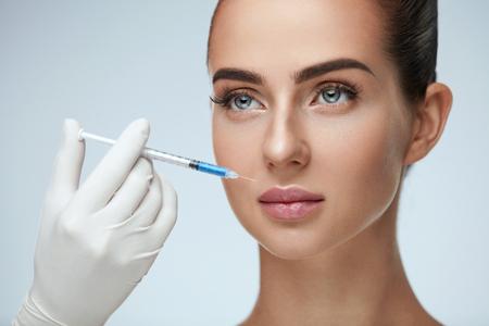 美容注射。注射器女性の顔の近くで医者の手のクローズ アップ。顔の皮膚を持ち上げる治療、注射を受けて柔らかい肌、完璧なメイクと美しい女性