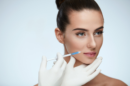 Plastic Surgery. Closeup Of Beautician Hands Holding Syringe Near Female Facial Skin Doing Injections. Portrait Of Beautiful Young Woman Face Getting Hyaluronic Injection. Cosmetology. High Resolution