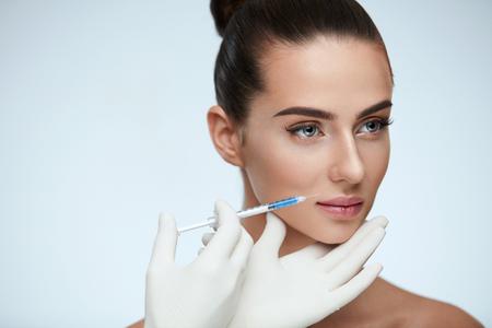 Plastische Chirurgie. Nahaufnahme der Kosmetikerin Hände Spritze in der Nähe von weiblichen Gesichtshaut Einspritzung zu halten. Porträt des schönen jungen Frauengesichtes, das Hyaluronic Einspritzung erhält. Kosmetologie. Hohe Auflösung Standard-Bild