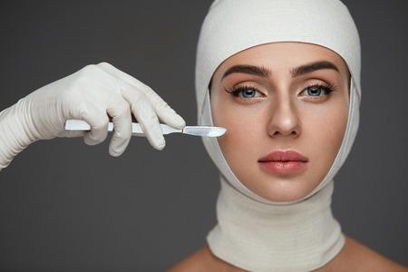 整形手術。滑らかな柔らかい肌と完璧なメイクの美しい若い女性の肖像画。包帯で頭と手にメスを持つ魅力的な女性患者のクローズ アップ。スキン