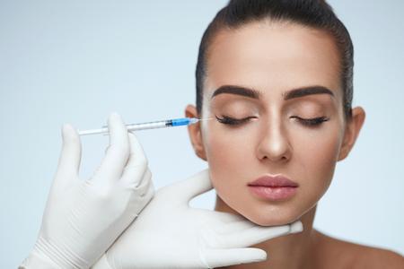 Cosmetische behandeling. Closeup schoonheidsspecialiste handen doen gezicht huid opheffing injectie naar Woman's gezicht. Mooie vrouw met gesloten ogen ontvangen schoonheidsprocedure binnenshuis. Plastische chirurgie. Hoge resolutie Stockfoto