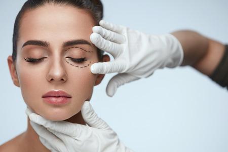 """Tratamento Facial. Retrato da mulher """"sexy"""" bonita com olhos fechados e linhas cirúrgicas pretas na pele. Closeup de mãos tocando o rosto feminino jovem. Conceito de cirurgia plástica. Alta resolução"""