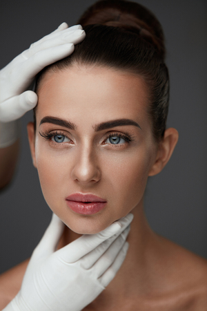 Beauty Woman Face. Portrait Beautiful Girl With Perfect Makeup And Smooth Soft Healthy Skin. Closeup Of Cosmetician Hands In Gloves Touching Young Woman Facial Skin. Plastic Surgery. High Resolution Banco de Imagens