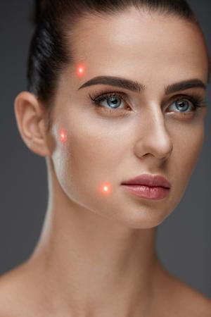 美容トリートメント。柔らかい肌と顔に赤いレーザー ポイントの美しい若い女性の肖像画。灰色の背景の整形手術の前にセクシーな健康な女性のク