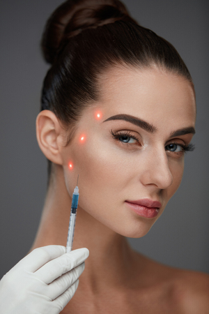 Skin Care. Closeup Of Hands Holding Syringe Near Sexy Young Female Patients Face. Portrait Of Beautiful Woman Receiving Hyaluronic Acid, Facial Skin Lift Injections. Plastic Surgery. High Resolution Stock Photo