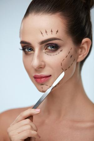 プラスチック外科手術。クローズ アップ メスを保持しているファッショナブルな化粧品で美しい若い女性。肖像画の顔に黒い線で健康的な女性モデ 写真素材