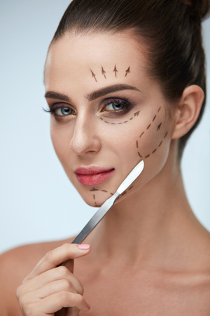 Plastic Surgery Operation. Closeup Beautiful Young Woman With Fashionable Makeup Holding Scalpel. Portrait Healthy Female Model With Black Lines On Face. Facial Beauty Treatment. High Resolution Stock Photo