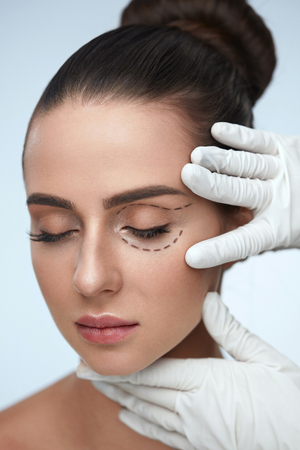 Facial Treatment. Portrait Of Beautiful Sexy Woman With Closed Eyes And Black Surgical Lines On Skin. Closeup Of Hands Touching Young Female Face. Plastic Surgery Concept. High Resolution Archivio Fotografico