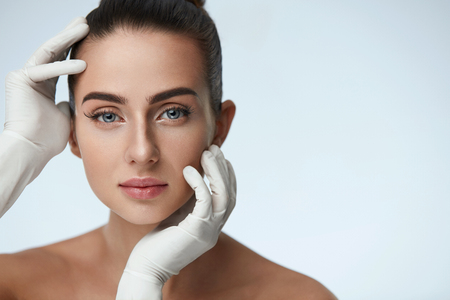 Cosmetology. Portrait Of Beautiful Woman Before Plastic Surgery Operation With Hands In Gloves Touching Her Beauty Face. Closeup Of Healthy Young Female With Soft Smooth Facial Skin. High Resolution Stock Photo - 75848727