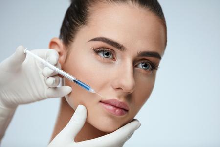 整形手術。美しさセクシーな女の子の唇ヒアルロン リップ注射を行う医師の手のクローズ アップ。化粧品治療室内の美しい若い女性の肖像画。皮膚 写真素材