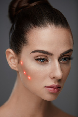 eye brow: Beauty Treatment. Portrait Of Beautiful Young Woman With Soft Skin And Red Laser Points On Face. Closeup Of Sexy Healthy Woman Before Plastic Surgery On Grey Background. Cosmetology. High Resolution Stock Photo