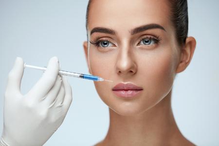 뷰티 인젝션. 여성 얼굴 근처 주사기와 의사의 근접 촬영 손. 부드러운 피부, 완벽 한 메이크업 얼굴 피부 리프팅 치료, 주입을받은 아름 다운 여자의  스톡 콘텐츠