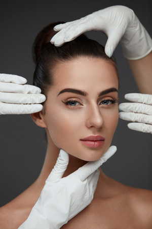 Mooi gezicht. Mooie vrouw vóór plastische chirurgieoperatie. De close-up dient Handschoenen in wat betreft Vrouwelijk Hoofd. Portret van een jonge vrouw met een gladde gezichtshuid. Cosmetologie en huidverzorging. Hoge resolutie