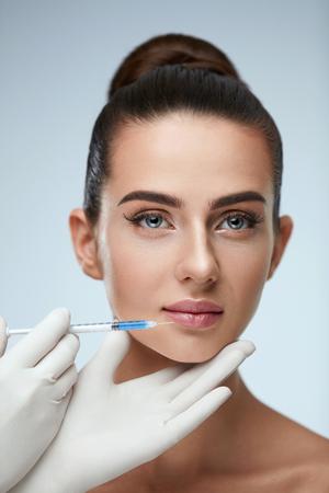 Chirurgia plastica. Closeup delle mani di Beautician tenendo siringa vicino alla pelle facciale femminile fare le iniezioni. Ritratto di bella giovane donna faccia ottenere iniezione ialuronica. Cosmetologia. Alta risoluzione Archivio Fotografico - 75898267