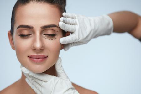 Tratamiento facial. Retrato de la mujer atractiva con los ojos cerrados y líneas quirúrgicos negros en la piel. Primer de las manos que tocan joven rostro femenino. Concepto de Cirugía Plástica. Alta resolución