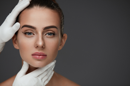 Beauty Woman Face. Portrait Beautiful Girl With Perfect Makeup And Smooth Soft Healthy Skin. Closeup Of Cosmetician Hands In Gloves Touching Young Woman Facial Skin. Plastic Surgery. High Resolution Banque d'images