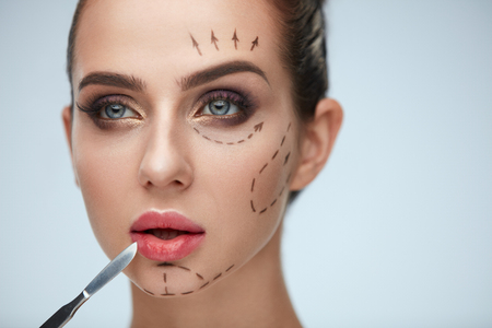 Plastic Surgery Operation. Closeup Beautiful Young Woman With Fashionable Makeup Holding Scalpel. Portrait Healthy Female Model With Black Lines On Face. Facial Beauty Treatment. High Resolution Фото со стока