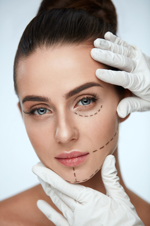 eyelids: Facial Beauty Treatment. Beautiful Young Female With Smooth Skin, Perfect Makeup And Surgical Lines. Closeup Of Beautician Hands Touching Woman Face Before Plastic Surgery Operation. High Resolution