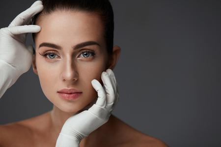 Cosmetologie. Portret van mooie vrouw vóór plastische chirurgie operatie met handen in handschoenen aan haar gezicht van de schoonheid aan te raken. Close-up van gezonde jonge vrouw met zachte gladde gezichtshuid. Hoge resolutie