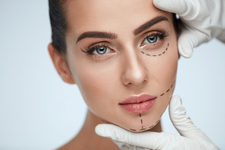 Facial Beauty Treatment. Beautiful Young Female With Smooth Skin, Perfect Makeup And Surgical Lines. Closeup Of Beautician Hands Touching Woman Face Before Plastic Surgery Operation. High Resolution Reklamní fotografie - 76061823