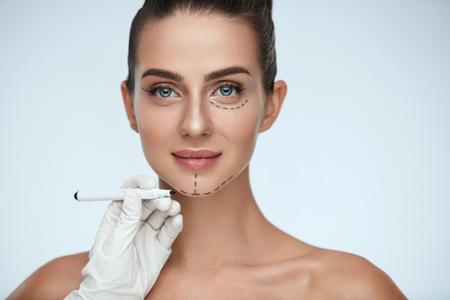 Schönheits-Operation. Nahaufnahme der Kosmetiker-Hand zeichnende chirurgische Linien auf schönem Gesicht der jungen Frau. Portrait der reizvollen Frau mit weicher Haut vor Schönheitsoperation. Gesichtsbehandlung. Hohe Auflösung