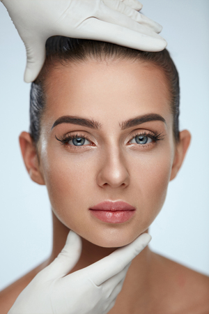顔の美しさ。完璧なメイクと柔らかな滑らかな肌の美しい若い女性の肖像画。セクシーな女性の顔に触れる手袋で美容師の手のクローズ アップ。整