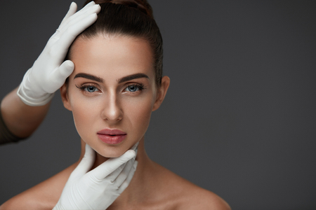 Beauty Woman Face. Portrait Beautiful Girl With Perfect Makeup And Smooth Soft Healthy Skin. Closeup Of Cosmetician Hands In Gloves Touching Young Woman Facial Skin. Plastic Surgery. High Resolution