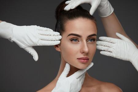 Bellezza del viso. Bella donna prima dell'operazione di chirurgia plastica. Closeup Mani In Guanti Toccando Testa Femminile. Ritratto Di Giovane Donna Con Pelle Facciale Liscia. Cosmetologia e cura della pelle. Alta risoluzione Archivio Fotografico - 76061867