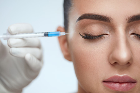 Cosmetic Treatment. Closeup Beautician Hands Doing Facial Skin Lifting Injection To Womans Face. Beautiful Female With Closed Eyes Receiving Beauty Procedure Indoors. Plastic Surgery. High Resolution