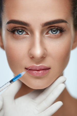 Plastic Surgery. Closeup Of Doctor Hands Doing Beauty Hyaluronic Lip Injection For Sexy Girl Lips. Portrait Of Beautiful Young Woman Getting Cosmetic Treatment Indoors. Skin Procedure. High Resolution Stock Photo