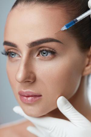 Chirurgia plastica. Primo piano di bella giovane donna che riceve le iniezioni facciali di bellezza. Mani in guanti che tengono la siringa che fa l'iniezione dell'acido ialuronico, procedura di bellezza sul fronte femminile. Alta risoluzione Archivio Fotografico - 75896375