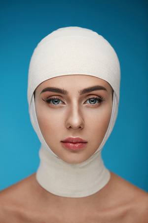 Plastic Surgery. Portrait Of Beautiful Young Woman With Head Wrapped In Medical Bandages. Closeup Of Healthy Woman Face With Smooth Soft Skin And Perfect Makeup. Cosmetic Treatment. High Resolution Stock Photo