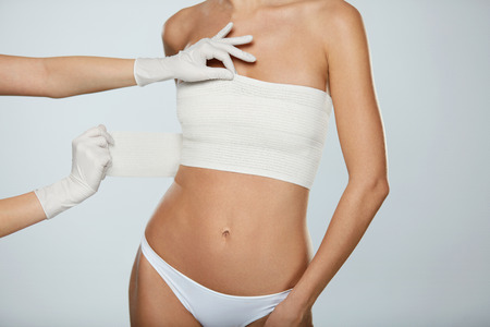 Body Plastic Surgery. Slim Young Female Body In White Panties And Breast Bandages On White Background. Closeup Of Doctor Hands In Gloves Wrapping Female Patients Breast In Bandage. High Resolution