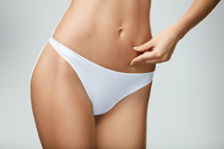 vientre femenino: Perfect Shape. Hot Slim Young Woman Body In White Panties Posing On Grey Background. Closeup Of Female Hand Pinching Fit Pumped Belly, Abdomen. Fitness Concept. High Resolution