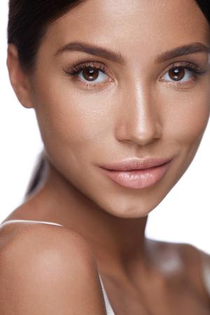Schönheits-Gesicht. Nahaufnahme der gesunden jungen Frau des Brunette mit frischer weicher glatter Haut auf weißem Hintergrund. Porträt des schönen sexy weiblichen Modells mit perfektem Make-up. Facial? Osmetics. Hohe Auflösung Standard-Bild - 76406703