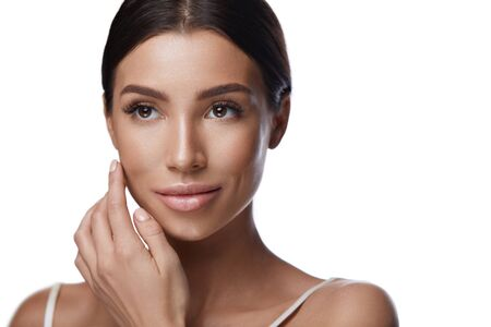 Facial Cosmetics. Closeup Of Sexy Young Woman With Soft Smooth Skin And Hand Near Face. Portrait Of Beautiful Healthy Female With Professional Makeup Touching Skin. Natural Beauty. High Resolution