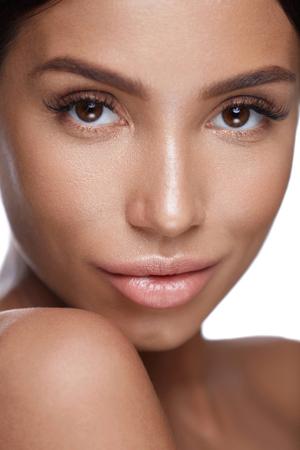 Cara De La Belleza. Closeup de morena Mujer joven saludable con suave suave suave de la piel sobre fondo blanco. Retrato De Hermosa Modelo Femenino Sexy Con Maquillaje Perfecto. Cosméticos faciales. Alta resolución Foto de archivo - 76405147