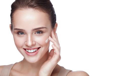 Cosmétiques pour la peau. Portrait de belle jeune fille appliquant une base de crème tonique sur le visage. Gros plan de femme souriante avec une peau saine pure et un maquillage professionnel parfait. Beauté du visage. Haute résolution Banque d'images