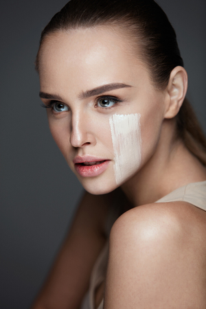 Foundation. Closeup Of Attractive Young Woman With Stripe Of Skin Tone Cream On Face. Portrait Of Beautiful Sexy Girl With Natural Fresh Makeup And Perfect Soft Skin. Skin Care. High Resolution Stock Photo