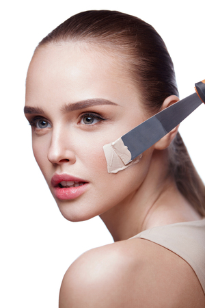 Facial Cosmetics. Portrait Of Young Female Model Applying Foundation With Spatula. Closeup Of Beautiful Young Woman With Smooth Skin And Perfect Professional Makeup. Beauty Concept. High Resolution Stock Photo